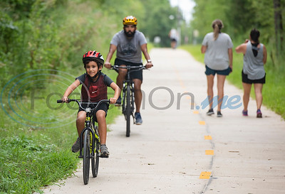 Evan Serrato, 7, of Tyler, rides his bike in front of his dad, Zibeon Serrato, on the Legacy Trails during the grand opening event for Legacy Trails in Tyler. The new paved trail offers space for bicyclists, hikers and walkers to exercise between Tyler and Gresham.   (Sarah A. Miller/Tyler Morning Telegraph)
