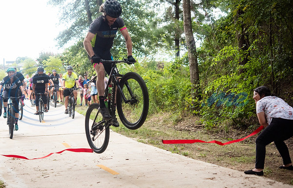 Nevada Thompson jumps his bicycle over the red ribbon during the grand opening event for Legacy Trails at the Legacy Trails Trailhead at Old Jacksonville Highway and Three Lakes Parkway in Tyler. The new paved trail offers space for bicyclists, hikers and walkers to exercise between Tyler and Gresham.   (Sarah A. Miller/Tyler Morning Telegraph)