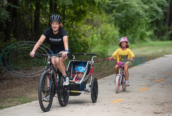 Jennifer Hoitsma of Tyler rides her bike with daughter Lucy, 3, in tow and Penelope, 7, on her own bike on the Legacy Trails during the grand opening event for Legacy Trails in Tyler. The new paved trail offers space for bicyclists, hikers and walkers to exercise between Tyler and Gresham.   (Sarah A. Miller/Tyler Morning Telegraph)