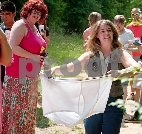 photo by Sarah A. Miller/Tyler Morning Telegraph  Camp Kennedy recreation director Madison Hill, right, shows campers a discarded pair of Big Foot's underpants found along a trail during the campers' daily Big Foot hunt Wednesday. Camp Kennedy is a camp for adults with special needs held on the campus of Tyler Metro Church's Stonefort Camp. Big Foot visits the cam each year making appearances at several camp events.