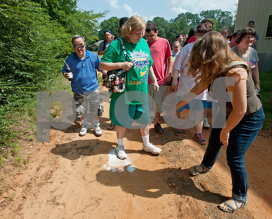 photo by Sarah A. Miller/Tyler Morning Telegraph  Camp Kennedy recreation director Madison Hill, right, points out footprints from Big Foot along a path during the campers' daily Big Foot hunt Wednesday. Camp Kennedy is a camp for adults with special needs held on the campus of Tyler Metro Church's Stonefort Camp. Big Foot visits the cam each year making appearances at several camp events.