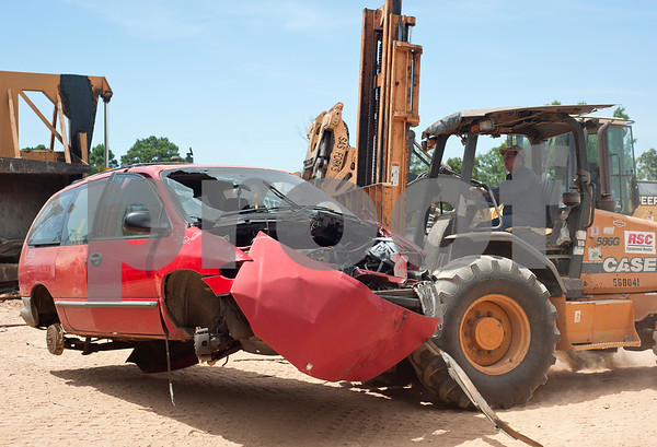 David Villa moves a minivan on the lot at Locos Gringos Pick-n-Pull Tuesday July 21, 2015. Locos Gringos, 10310 County Road 383 in Tyler, is an auto recycler that buys vehicles and sells them for parts in their self-service lot. They have about 900 automobiles on their 14 acre property.  (photo by Sarah A. Miller/Tyler Morning Telegraph)