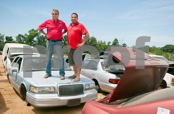"""Locos Gringos Pick-n-Pull owners Gerald Scott and Rick Sage stand on the hood of a car Tuesday July 21, 2015 in their large lot of self-serve car parts. Locos Gringos held their famous """"all you can carry"""" sale Saturday July 25 where hundreds of customers purchased all the items they could carry off the lot for $75.   (photo by Sarah A. Miller/Tyler Morning Telegraph)"""