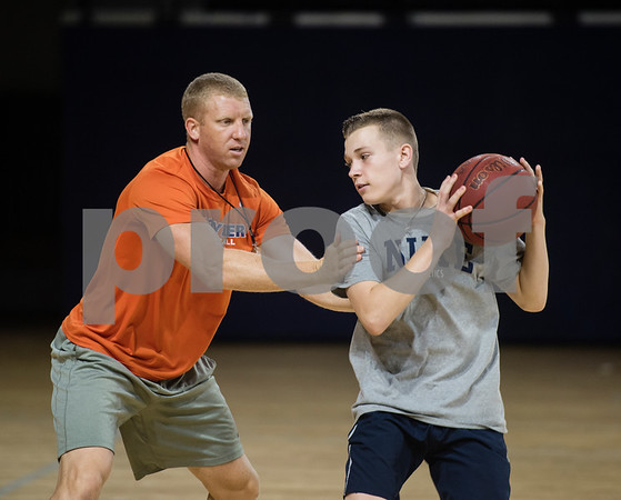 Jamon Copeland, head men's basketball coach at UT-Tyler, uses camper Jake Carlile, 15, in an example for a drill during a youth basketball camp held by the University of Texas at Tyler men's basketball coaching staff at the Louise Herrington Patriot Center. Campers learned skills such as shooting, ball handling and defense.  (Sarah A. Miller/Tyler Morning Telegraph)