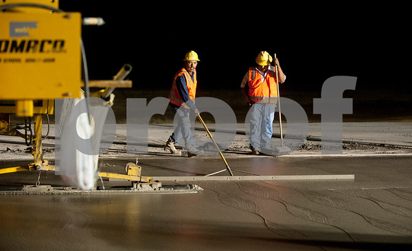 Workers smooth out new concrete on a section of runway 4-22 that is under construction Tuesday night at Tyler Pounds Regional Airport.  (photo by Sarah A. Miller/Tyler Morning Telegraph)