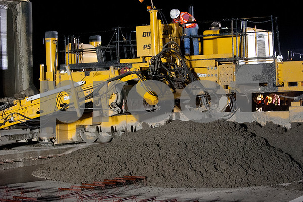 Concrete is poured over rods that will vibrate to expel air as a section of runway 4-22 is reconstructed Tuesday night at Tyler Pounds Regional Airport.  (photo by Sarah A. Miller/Tyler Morning Telegraph)