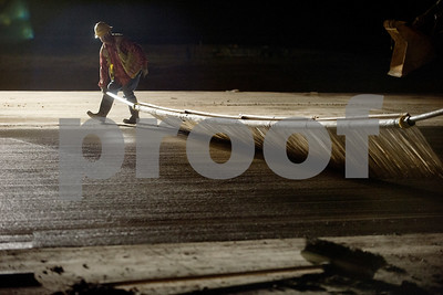Workers add a finishing texture to a section of runway 4-22 that is under construction Tuesday night at Tyler Pounds Regional Airport.  (photo by Sarah A. Miller/Tyler Morning Telegraph)