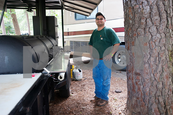 Brandon Robertson of Whitehouse is pictured next to his barbecue pit at his campsite at the Texas State Railroad Campground in Rusk Friday. The campground is the site of the  Texas Hobo Cook-Off & Gypsy Jamboree which is a partnership between the Cherokee 4-H Parent & Adult Leaders' Association and Texas State Railroad. Saturday's events will include several different barbecue cooking contests and a train ride.    (photo by Sarah A. Miller/Tyler Morning Telegraph)
