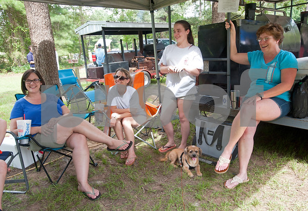 Kendall Thomas of Katy, Tammi Arnwine of Rusk, Kaylie Arnwine of Rusk and Lea Anne Lemon of Orange Grove relax at their campsite at the Texas State Railroad Campground in Rusk Friday. The campground is the site of the  Texas Hobo Cook-Off & Gypsy Jamboree which is a partnership between the Cherokee 4-H Parent & Adult Leaders' Association and Texas State Railroad. Saturday's events will include several different barbecue cooking contests and a train ride.    (photo by Sarah A. Miller/Tyler Morning Telegraph)