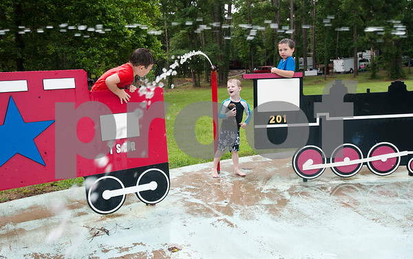 Lathan Campbell, 4, of Teneha, Mitchell Moore, 4, of Tomball and Gus Severn, 6, of Palestine, play on the train themed splash ground at the Texas State Railroad Campground in Rusk Friday. The campground is the site of the  Texas Hobo Cook-Off & Gypsy Jamboree which is a partnership between the Cherokee 4-H Parent & Adult Leaders' Association and Texas State Railroad. Saturday's events will include several different barbecue cooking contests and a train ride.    (photo by Sarah A. Miller/Tyler Morning Telegraph)