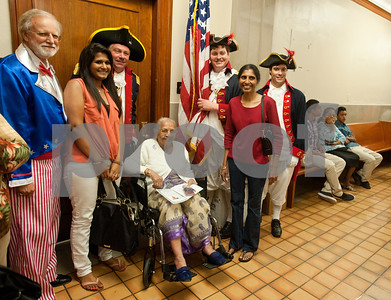 photo by Sarah A. Miller/Tyler Morning Telegraph  New United States citizen Tyler resident Jiviben Patel, formerly of India, center, has her photograph taken with her granddaughter Shivani Patel and daughter Mauyri Patel and a host of patriotically dressed men after her naturalization ceremony Wednesday in Tyler.