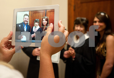 photo by Sarah A. Miller/Tyler Morning Telegraph  New United States citizen Longview resident Anthony Keller, formerly of Great Britain, and his wife Johanna Keller have their photograph taken on an iPad with Judge Judith Guthrie after their naturalization ceremony Wednesday.