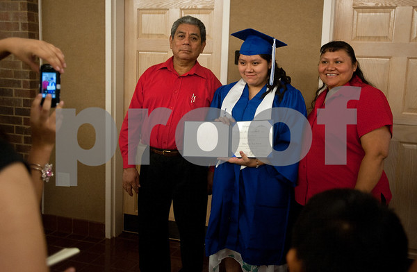 photo by Sarah A. Miller/Tyler Morning Telegraph  John Tyler High School student Haide Gregorio holds her diploma as she has her photograph taken with her parents Filogonio and Minerva Gregorio Thursday during the TISD summer commencement ceremony. Students who were ineligible for the traditional spring ceremony were able to take summer school classes and retest for the summer commencement.