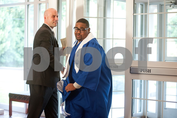 photo by Sarah A. Miller/Tyler Morning Telegraph  TISD executive director of secondary education Joe Coburn holds the door open for John Tyler High School student Christopher Starling as he arrives at the let minute Thursday before the TISD summer commencement ceremony began. Students who were ineligible for the traditional spring ceremony were able to take summer school classes and retest for the summer commencement which was held at the UT-Tyler Ornelas Activity Center.