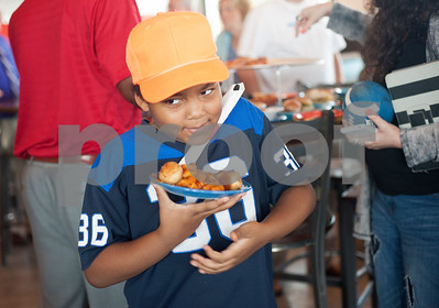 Daniel Reed, 8, of Tyler, carries a plate of Tyler Rose Pasta, a dish featuring Earl Campbell's smoked sausage during a kick-off event for Earl Campbell Signature Dishes at Rotolo's Pizzeria in Tyler Tuesday Aug. 18, 2015. The new dishes, including a pizza, sandwich, calzone and pasta feature Earl Campbell brand smoked sausage. Campbell is a former professional football player and Heisman Trophy winner from Tyler.   (Sarah A. Miller/Tyler Morning Telegraph)