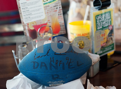 A fan's autographed football sits on a table as people eat during a kick-off event for Earl Campbell Signature Dishes at Rotolo's Pizzeria in Tyler Tuesday Aug. 18, 2015. The new dishes, including a pizza, sandwich, calzone and pasta feature Earl Campbell brand smoked sausage. Campbell is a former professional football player and Heisman Trophy winner from Tyler.   (Sarah A. Miller/Tyler Morning Telegraph)