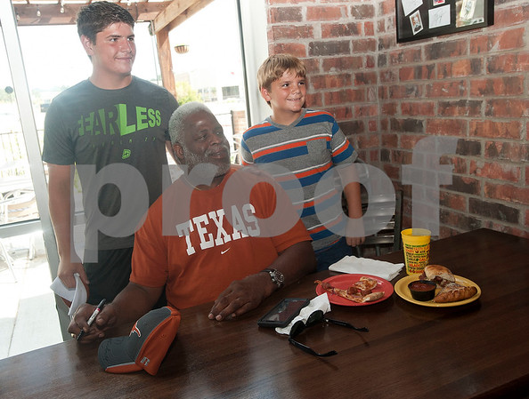 Kasey Cockrell, 15, and Klayden Cockrell, 11, both of Kemp, have their photograph taken with Earl Campbell during a kick-off event for Earl Campbell Signature Dishes at Rotolo's Pizzeria in Tyler Tuesday Aug. 18, 2015. The new dishes, including a pizza, sandwich, calzone and pasta feature Earl Campbell brand smoked sausage. Campbell is a former professional football player and Heisman Trophy winner from Tyler.   (Sarah A. Miller/Tyler Morning Telegraph)