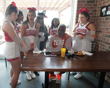 Earl Campbell gives his autograph to Robert E. Lee High School cheerleaders during a kick-off event for Earl Campbell Signature Dishes at Rotolo's Pizzeria in Tyler Tuesday Aug. 18, 2015. The new dishes, including a pizza, sandwich, calzone and pasta feature Earl Campbell brand smoked sausage. Campbell is a former professional football player and Heisman Trophy winner from Tyler.   (Sarah A. Miller/Tyler Morning Telegraph)