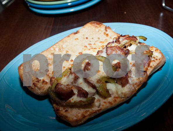 An Earl Campbell sausage sandwich waits to be eaten during a kick-off event for Earl Campbell Signature Dishes at Rotolo's Pizzeria in Tyler Tuesday Aug. 18, 2015. The new dishes, including a pizza, sandwich, calzone and pasta feature Earl Campbell brand smoked sausage. Campbell is a former professional football player and Heisman Trophy winner from Tyler.   (Sarah A. Miller/Tyler Morning Telegraph)