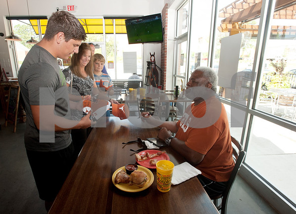 Kasey Cockrell, 15, Kendra Thompson and Klayden Cockrell, 11, all of Kemp, meet Earl Campbell during a kick-off event for Earl Campbell Signature Dishes at Rotolo's Pizzeria in Tyler Tuesday Aug. 18, 2015. The new dishes, including a pizza, sandwich, calzone and pasta feature Earl Campbell brand smoked sausage. Campbell is a former professional football player and Heisman Trophy winner from Tyler.   (Sarah A. Miller/Tyler Morning Telegraph)