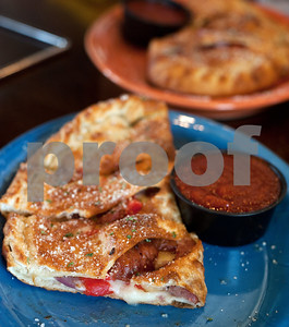 An Earl Campbell sausage calzone waits to be eaten during a kick-off event for Earl Campbell Signature Dishes at Rotolo's Pizzeria in Tyler Tuesday Aug. 18, 2015. The new dishes, including a pizza, sandwich, calzone and pasta feature Earl Campbell brand smoked sausage. Campbell is a former professional football player and Heisman Trophy winner from Tyler.   (Sarah A. Miller/Tyler Morning Telegraph)