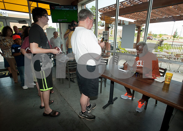 Earl Campbell signs autographs for fans during a kick-off event for Earl Campbell Signature Dishes at Rotolo's Pizzeria in Tyler Tuesday Aug. 18, 2015. The new dishes, including a pizza, sandwich, calzone and pasta feature Earl Campbell brand smoked sausage. Campbell is a former professional football player and Heisman Trophy winner from Tyler.   (Sarah A. Miller/Tyler Morning Telegraph)