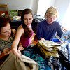 Mackenzie Combs (right), freshman in architecture, get help unpacking his clothing from his sister Emily Combs (left) and friend Kayla Morrisey (middle) while settling into his room in Hallett Hall during early move in at the University of Colorado in Boulder, Colorado August 21, 2012.  DAILY CAMERA MARK LEFFINGWELL