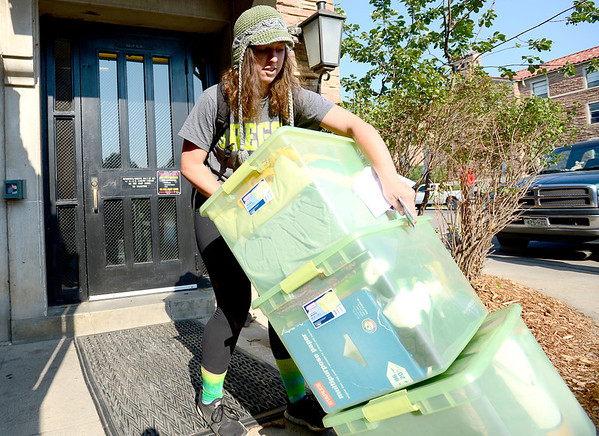 Caroline Atsaves, freshman in international affairs, muscles her stuff up the step the door at Farrand Hall during early move in at the University of Colorado in Boulder, Colorado August 21, 2012.  DAILY CAMERA MARK LEFFINGWELL