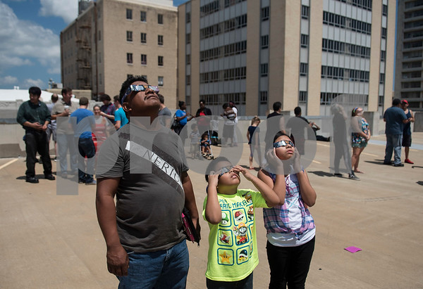 Juan Sanchez, Juan Sanchez Jr., 7, and Dulce Sanchez, 9, of Tyler, use glass to view the partial solar eclipse seen over Tyler, Texas from the Fair Plaza Parking Garage Monday Aug. 21, 2017.  (Sarah A. Miller/Tyler Morning Telegraph)