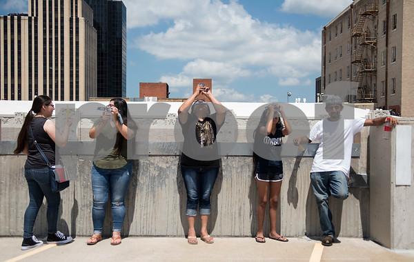 People watch the partial solar eclipse seen over Tyler, Texas from the Fair Plaza Parking Garage Monday Aug. 21, 2017.  (Sarah A. Miller/Tyler Morning Telegraph)