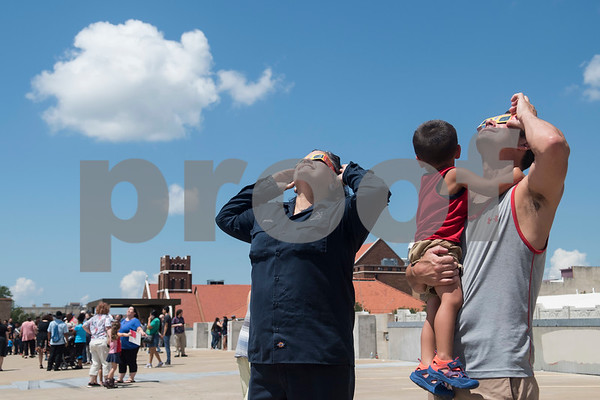 Jennifer Ducote, Brian Falgout and Caleb Fallout, 2, use glasses to view the partial solar eclipse seen over Tyler, Texas from the Fair Plaza Parking Garage Monday Aug. 21, 2017.  (Sarah A. Miller/Tyler Morning Telegraph)