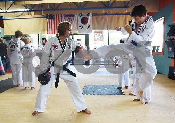 Christina Hill works with Joshua Hermanns, 8, during a taekwondo class at Songahm Martial Arts Academy in Tyler Wednesday August 10, 2016. Hermanns takes the classes with his brother Matthew, 13, and mother Dr. Melinda Hermanns.  (Sarah A. Miller/Tyler Morning Telegraph)
