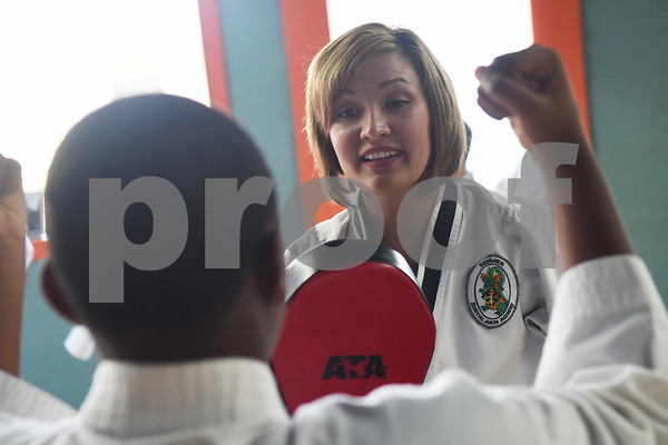 Christina Hill works with Kentrell Nelson, 11, during a taekwondo class at Songahm Martial Arts Academy in Tyler Wednesday August 10, 2016. Hill is married to Master Instructor Dr. Dometrius D. Hill.  (Sarah A. Miller/Tyler Morning Telegraph)