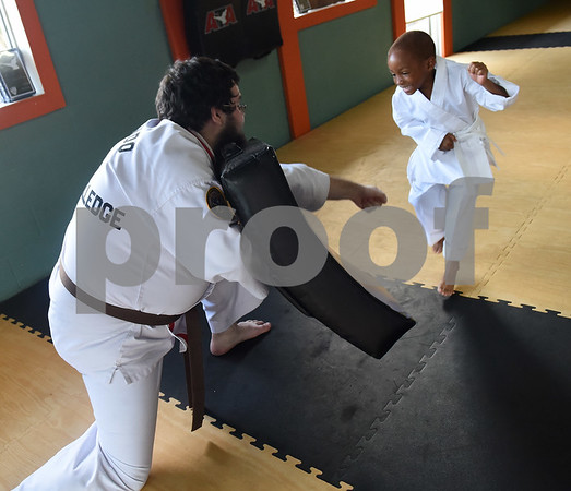 Trainee instructor Jonathan Elledge works with student Kemariee Evertt, 5, during a taekwondo class at Songahm Martial Arts Academy in Tyler Wednesday August 10, 2016. The academy focuses not only on martial arts but also on after school tutoring and leadership development.  (Sarah A. Miller/Tyler Morning Telegraph)
