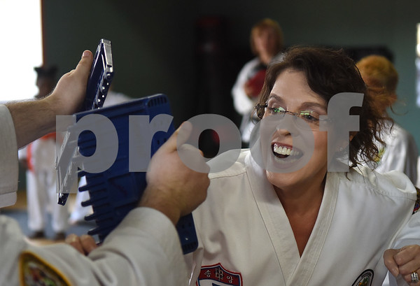 University of Texas at Tyler associate professor Dr. Melinda Hermanns breaks a board during a taekwondo class at Songahm Martial Arts Academy in Tyler Wednesday August 10, 2016. Hermanns takes the classes with her sons Joshua, 8, and Matthew, 13.  (Sarah A. Miller/Tyler Morning Telegraph)
