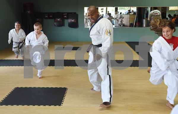 Master Instructor Dr. Dometrius D. Hill, center, encourages his students to run hard at the end of practice during a taekwondo class at Songahm Martial Arts Academy in Tyler Wednesday August 10, 2016. Hill is also Dean of Students at Tyler Junior College.  (Sarah A. Miller/Tyler Morning Telegraph)