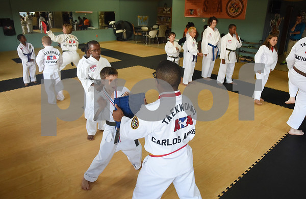 Trainee Instructor Carlos Arriola holds a board for students to break during a taekwondo class at Songahm Martial Arts Academy in Tyler Wednesday August 10, 2016.   (Sarah A. Miller/Tyler Morning Telegraph)