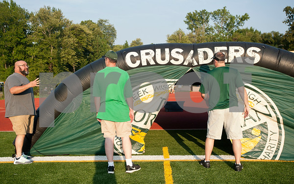 Robbie Chiasson's father Robert Chiasson, left, helps inflate the Bishop T.K. Gorman football tunnel before their game against Eustace Friday night Aug. 28, 2015. The Chiasson family evacuated to East Texas during Hurricane Katrina. They lived in St. Bernard Parish.    (Sarah A. Miller/Tyler Morning Telegraph)