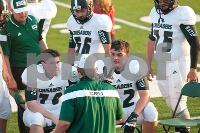 Robbie Chiasson (72), right, gets advice from his Bishop T.K. Gorman football coach during their game against Eustace Friday night Aug. 28, 2015. The Chiasson family evacuated to East Texas during Hurricane Katrina. They lived in St. Bernard Parish.    (Sarah A. Miller/Tyler Morning Telegraph)
