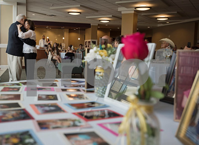 A table filled with family photos sits in the foreground as Judy and W.H. Harbour of Tyler dance at 50th wedding anniversary vow renewal ceremony at Green Acres Baptist Church on Saturday Aug. 4, 2018.   (Sarah A. Miller/Tyler Morning Telegraph)