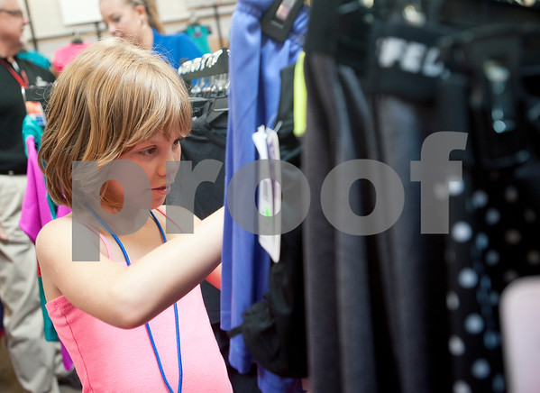 Paige Ross, 11, of Whitehouse, looks at a rack of clothing as she goes on a back-to-school shopping spree Wednesday at Academy Sports + Outdoors Tyler. Ross was one of 29 students from the YMCA Summer Day Camp who received a $100 gift card to shop for back to school items including  backpacks, footwear and lunch totes at Academy Sports + Outdoors.  (photo by Sarah A. Miller/Tyler Morning Telegraph)