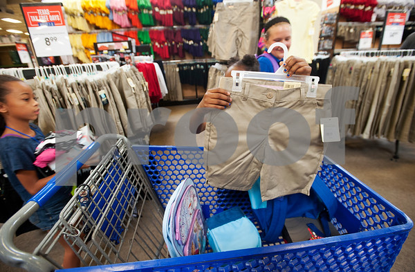 Malia Van Zandt, 7, of Tyler, gets a pair of uniform shorts during a shopping spree Wednesday at Academy Sports + Outdoors Tyler. Van Zandt was one of 29 students from the YMCA Summer Day Camp who received a $100 gift card to shop for back to school items including  backpacks, footwear and lunch totes at Academy Sports + Outdoors.  (photo by Sarah A. Miller/Tyler Morning Telegraph)