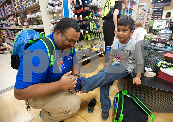 Sales associate Christian Noyola helps Adriel Vasquez, 5, of Tyler try on a pair of shoes during a back-to-school shopping spree Wednesday at Academy Sports + Outdoors Tyler. Vasquez was one of 29 students from the YMCA Summer Day Camp who received a $100 gift card to shop for back to school items including  backpacks, footwear and lunch totes at Academy Sports + Outdoors.  (photo by Sarah A. Miller/Tyler Morning Telegraph)