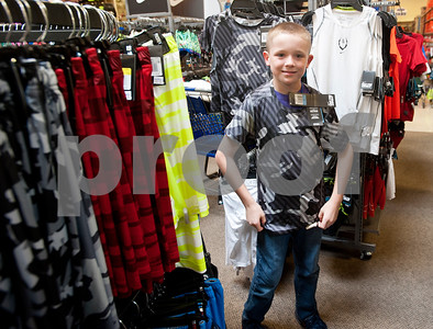 Kaleb Hawkins, 9, of Tyler tries on a shirt during a back-to-school shopping spree Wednesday at Academy Sports + Outdoors Tyler. Hawkins was one of 29 students from the YMCA Summer Day Camp who received a $100 gift card to shop for back to school items including  backpacks, footwear and lunch totes at Academy Sports + Outdoors.  (photo by Sarah A. Miller/Tyler Morning Telegraph)