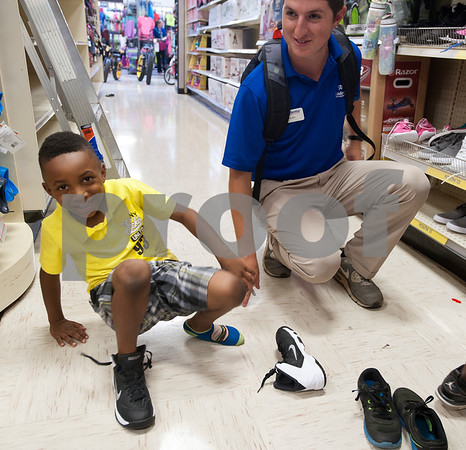 Micah Simpson, 5, of Tyler tries on shoes with help from store associate Colby Carpenter during a back-to-school shopping spree Wednesday at Academy Sports + Outdoors Tyler. Simpson was one of 29 students from the YMCA Summer Day Camp who received a $100 gift card to shop for back to school items including  backpacks, footwear and lunch totes at Academy Sports + Outdoors.  (photo by Sarah A. Miller/Tyler Morning Telegraph)