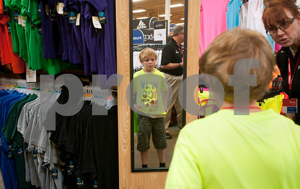 Sales associate Tina Henderson asks Avery Hawkins, 11, of Tyler, if he likes a shirt he tried on during a back-to-school shopping spree Wednesday at Academy Sports + Outdoors Tyler. Hawkins was one of 29 students from the YMCA Summer Day Camp who received a $100 gift card to shop for back to school items including  backpacks, footwear and lunch totes at Academy Sports + Outdoors.  (photo by Sarah A. Miller/Tyler Morning Telegraph)