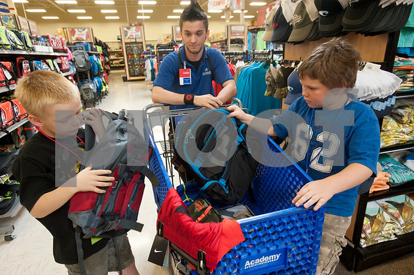 Store associate Justin White pushes a shopping cart as Tyler students Braydon Copeland, 7, and Hayden Padgett, 10, shop for backpacks during a back-to-school shopping spree Wednesday at Academy Sports + Outdoors Tyler. The brothers were two of 29 students from the YMCA Summer Day Camp who received $100 gift cards to shop for back to school items including  backpacks, footwear and lunch totes at Academy Sports + Outdoors.  (photo by Sarah A. Miller/Tyler Morning Telegraph)