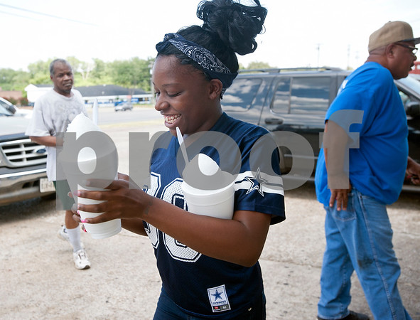 "Renea Henderson, 18, of Tyler, has her hands full with three large plain snow cones from Gentry Snowballs in Tyler Tuesday Aug. 4, 2015. ""This is a good place to go when it's hot,"" she said. Gentry Snowballs is open from noon to 7 p.m. seven days a week during the summer season.    (photo by Sarah A. Miller/Tyler Morning Telegraph)"