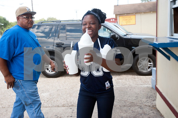 """Renea Henderson, 18, of Tyler, has her hands full with three large plain snow cones from Gentry Snowballs in Tyler Tuesday Aug. 4, 2015. """"This is a good place to go when it's hot,"""" she said. Gentry Snowballs is open from noon to 7 p.m. seven days a week during the summer season.    (photo by Sarah A. Miller/Tyler Morning Telegraph)"""