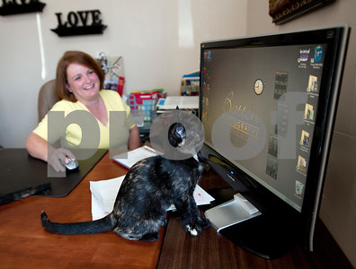 photo by Sarah A. Miller/Tyler Morning Telegraph  Franice Hodges of Tyler plays with a rescue cat by moving around a digital clock on her computer monitor at her office at Batten's Photogem.